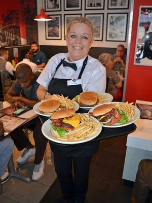 Steak 'n Shake waitress Kimberly Gambill prepares to serve customers burgers and fries.