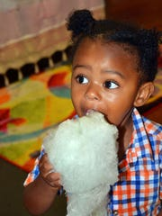 Houston Jones, 23 months, enjoys some grape-flavored cotton candy.