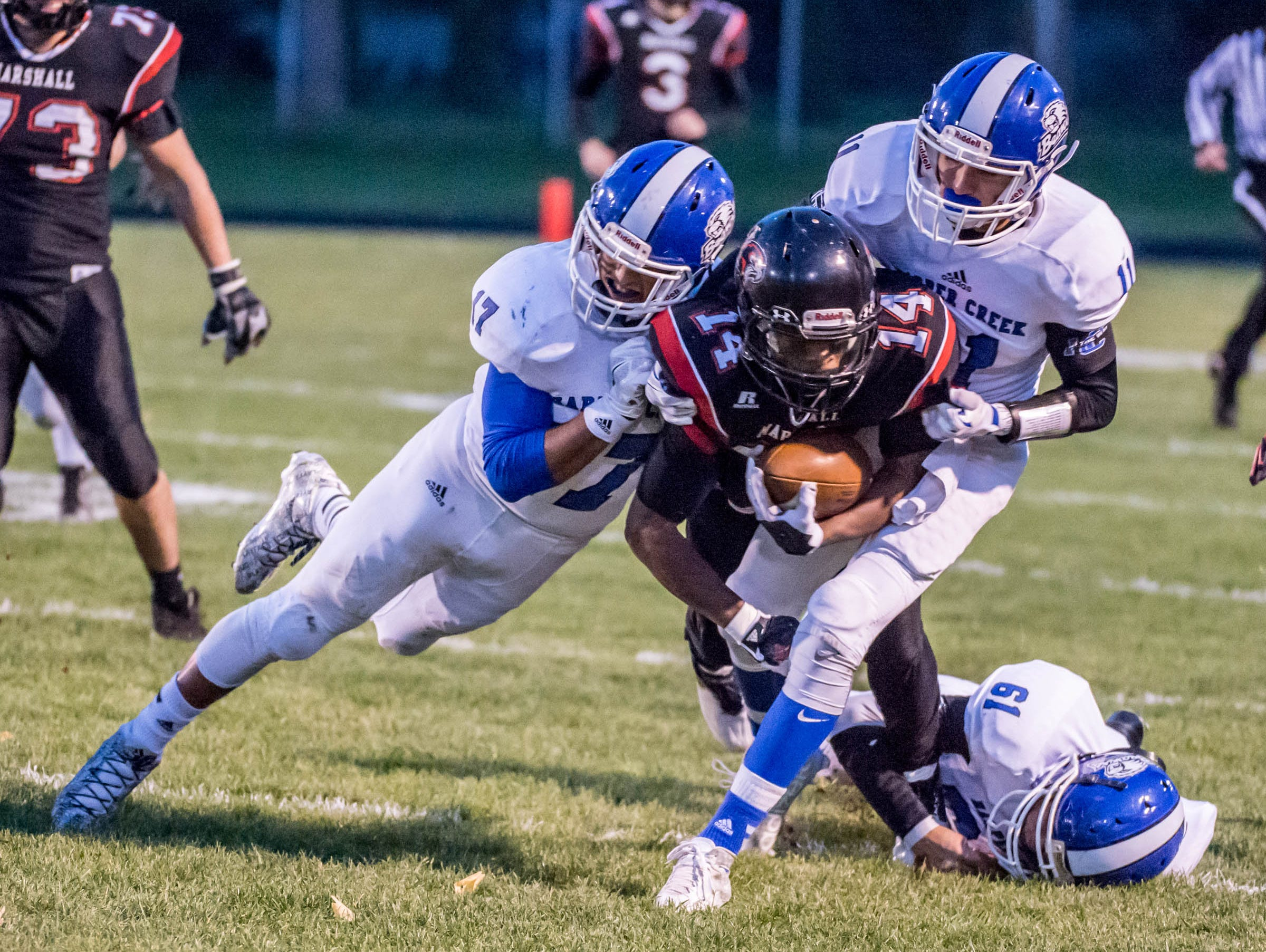 Marshall's Forrest Jackson advances the ball against Harper Creek.