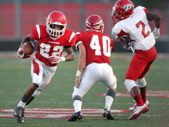 Fishers cornerback Jeremy Chinn runs back a ball he intercepted from Pike's Quentin Taliaferro in the first half of the game held at Fishers High School on Friday, August 29, 2014.