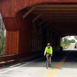 Dan Sheridan bicycles across the King's Mill Covered Bridge.