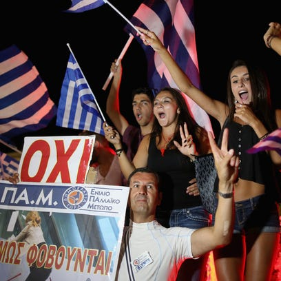 People celebrate in front of the Greek parliament as