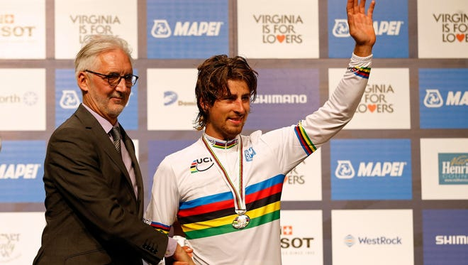 Peter Sagan of Slovakia (R) is congratulated by UCI president Brian Cookson (L) after receiving the gold medal in the men's elite race as part of the UCI road world championships 2015 at the Richmond Road Circuit.