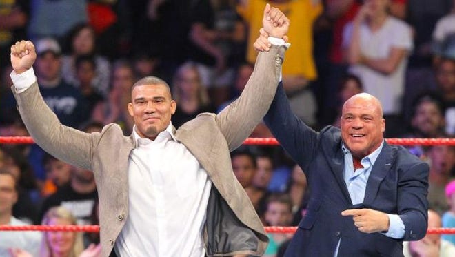 Indiana University graduate Jason Jordan, left, has his hand raised by WWE hall of famer Kurt Angle on Monday Night RAW.