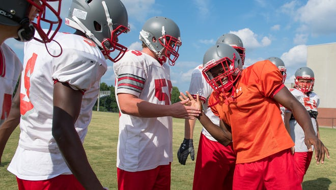 Wade Hampton quarterback Josh Edwards (5) high fives his offensive line during the teams practice on Wednesday, August 24, 2016.