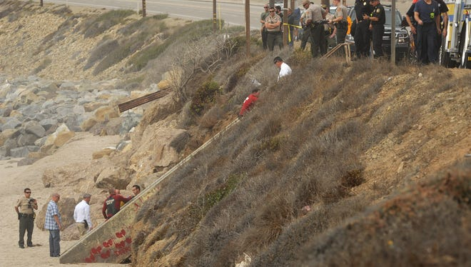 A Los Angeles County Fire Department lifeguard walks up stairs after helping retrieve a body found floating Thursday just off the coast at Deer Creek Road and the Pacific Coast Highway.