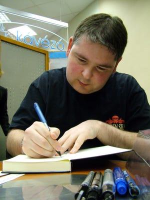 Irish writer Darren Shan signs his a book in Budapest, Hungary in April 2005.