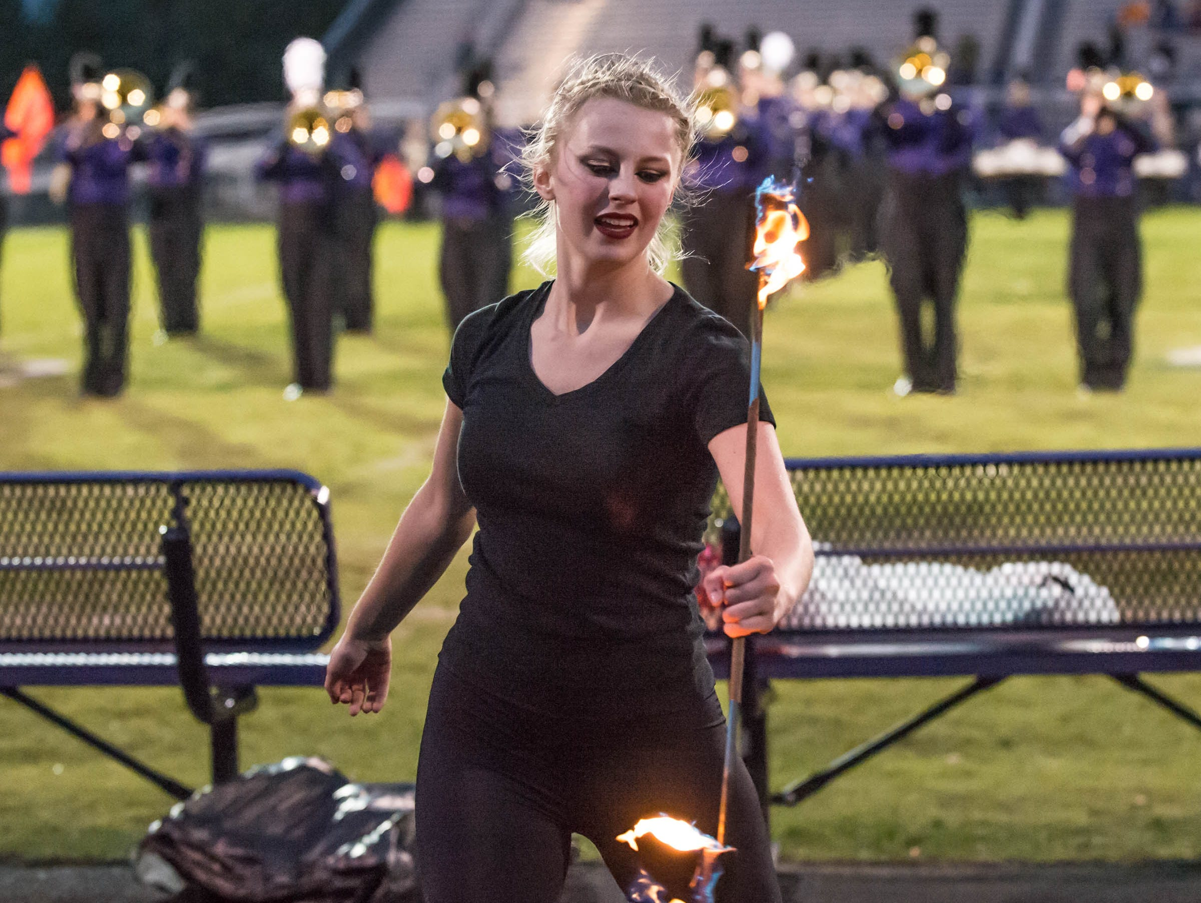 Maddie Etheridge performs with a flaming baton during the pre-game show at Lakeview Friday evening.