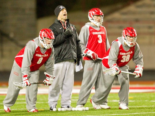 From left to right, are freshman Matt Taylor, coach Jeff Tambroni, sophomore Rob Pannell, 3, and freshman Tom Trasolini during the first practice of the Cornell men's lacrosse season at Schoellkopf Field in 2010.