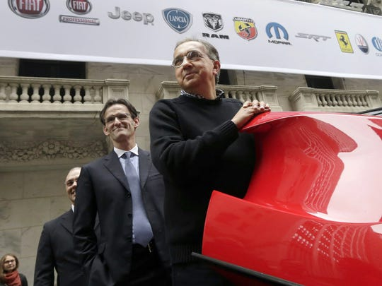 FCA CEO Sergio Marchionne, right, with company CFO Richard Palmer, closes the door of a Ferrari LaFerrari, outside the New York Stock Exchange, after he rang the closing bell in October 2014.