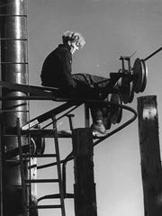 Historic photo shows maintenance on one of Okemo's early overhead chairlifts.