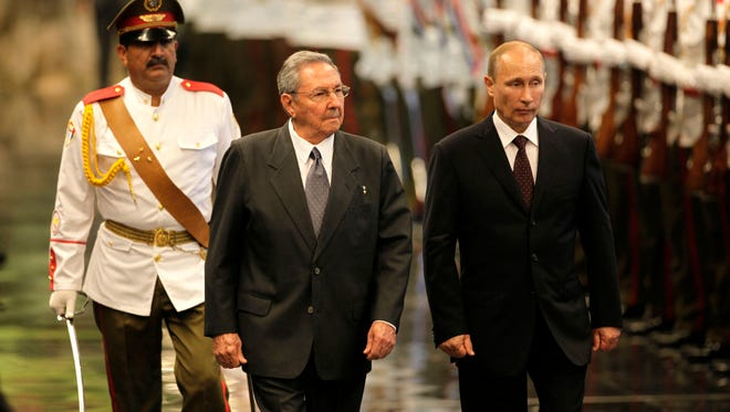 Cuban President Raul Castro, center, and Russian President Vladimir Putin review troops during a welcoming ceremony at Revolution Palace in Havana on July 11, 2014.