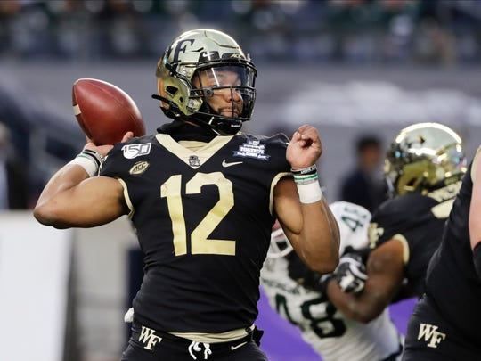 Wake Forest's Jamie Newman (12) throws a pass during the first half of the Pinstripe Bowl NCAA college football game against Michigan State, Friday, Dec. 27, 2019, in New York. (AP Photo/Frank Franklin II)