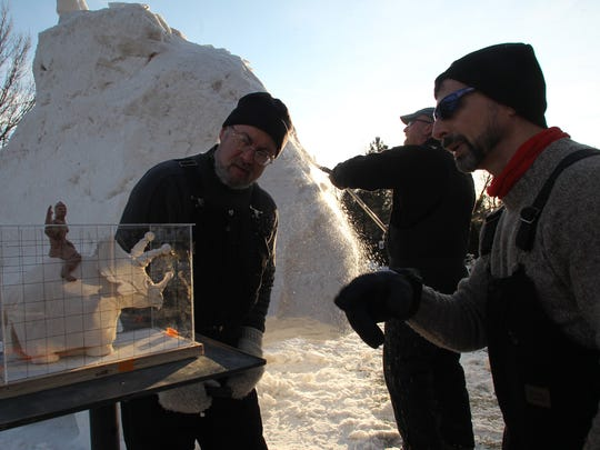 Team USA Snow Sculptors, from left, Michael Sponholtz, Milwaukee, Tom Queoff, Milwaukee, and Mike Martino, La Crosse, work on turning the model of a boy riding a ticeratops, left, into a snow sculpture, Thursday, February 9, 2012, at the Woodson Art Museum in Wausau.