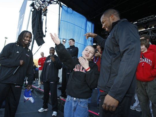 """fan, and adopted """"Little Brother"""" Mitch Stone sends a big kiss to fans as he is surrounded by players, including Mardy Gilyard, left, and Alex Daniels, right, during the Allstate Sugar Bowl Fan Fest held in the French Quarter in New Orleans, Louisiana Thursday Dec. 31, 2009."""