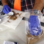 EPA officials only touch samples of buried battery casings with gloves. The casings contain lead, which has been found in high levels in the ground of some neighborhood properties.