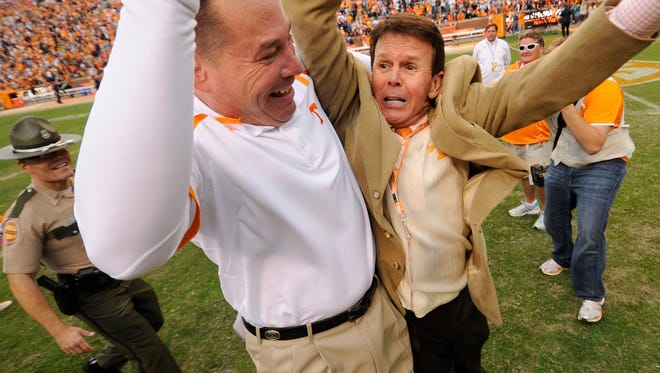 Former Vols football coach Butch Jones celebrates with former athletic director Dave Hart after Tennessee beat South Carolina 23-21 on Oct. 19, 2013.