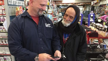 """Mike Flood and Tommy """"Spoons"""" Woodard look at a photo of Woodard's new trike. Flood bought a new trike for Woodard after someone stole his old one."""