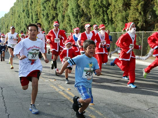 Runners take off in the Santa Paws 5K run/walk in Palm Springs on December 20, 2014. The event benefits the Guide Dogs of the Desert.