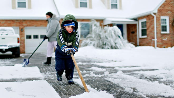 Aiden Weisz, 4, front, helps his mother Nicole Weisz, to shovel the driveway following early morning snowfall in Springettsbury Township, Thursday, Feb. 9, 2017. Dawn J. Sagert photo