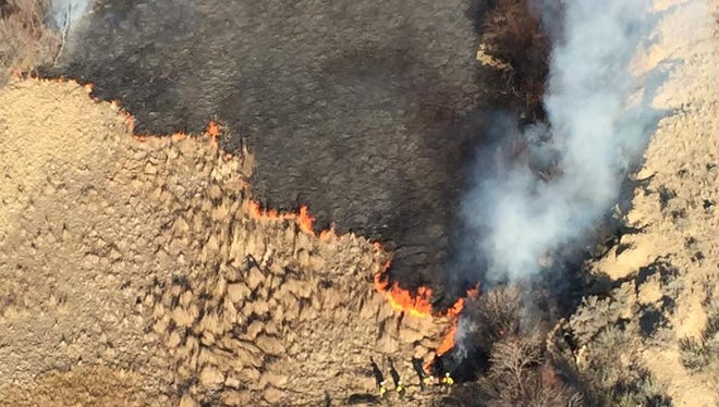 The San Juan County Sheriff's Office dispatched a helicopter Sunday afternoon to track a brush fire that broke out in the Hogback area, which is seen in this photograph. Navajo police are investigating the cause of the fire.
