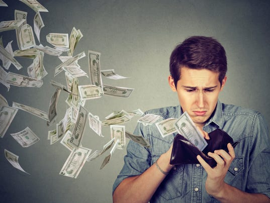 Man looking at wallet with money dollars flying away