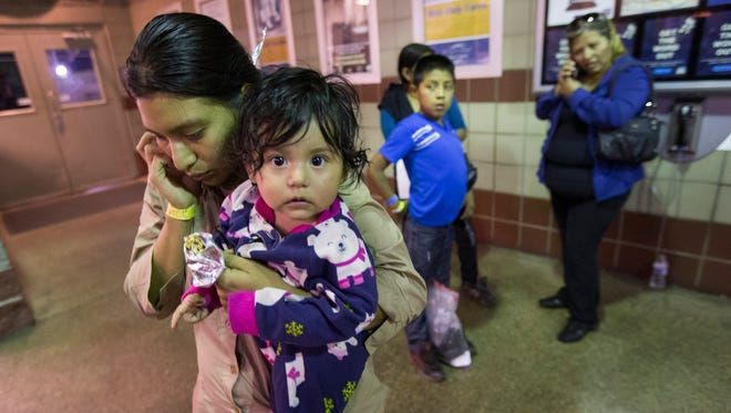 Judy Elizabeth Martinez, holding Marjorie, tries to reach family after being released by ICE at a Greyhound Bus station in Phoenix May 28, 2014. She is from Guatemala and was flown from Texas to Arizona by ICE. The Border Patrol says about 400 migrants were flown from Texas to Arizona because of surge in migrants being apprehended in Texas.