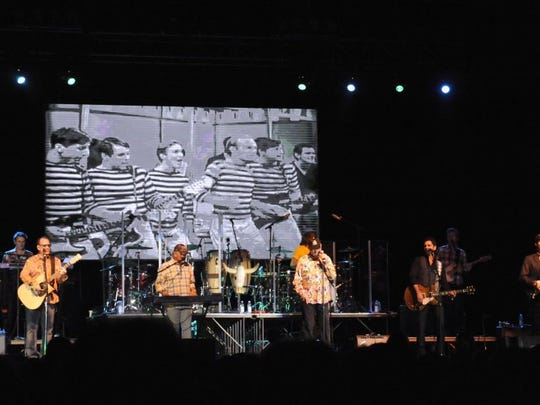 The Beach Boys perform four years ago in Abilene. Behind them is projected a television performance of the band from the 1960s.
