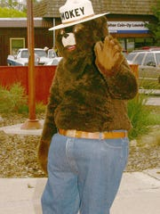 In this May 8, 2004 file photo a Smokey Bear character waves to visitors at the Smokey Bear Historical Park in his home town of Capitan, N.M.