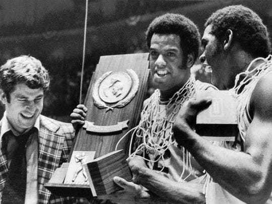 Indiana coach Bobby Knight, left, and team members Scott May, center, and Quinn Buckner, are all smiles as they hold the trophy for winning the NCAA Basketball championship in Philadelphia Monday night, March 30, 1976. (AP Photo/File)