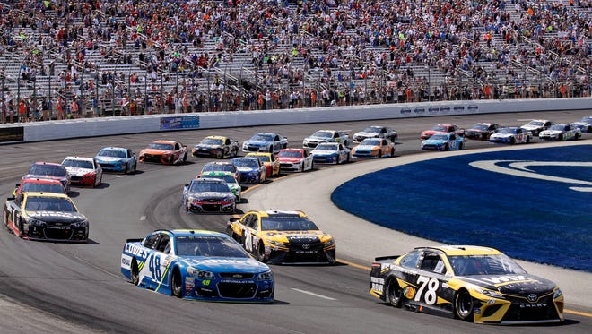 Driver Martin Truex Jr., bottom right, leads the pack going into the first turn of the NASCAR Cup Series 301 auto race at the New Hampshire Motor Speedway in Loudon, N.H., Sunday, July 16, 2017.