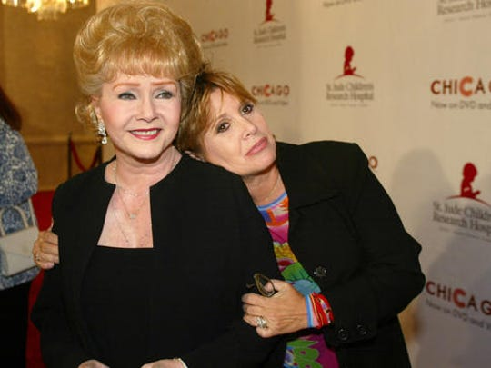"FILE - In this Tuesday, Aug. 19, 2003 file photo, Debbie Reynolds and Carrie Fisher arrive at the ""Runway for Life"" Celebrity Fashion Show Benefitting St. Jude's Children's Research Hospital and celebrating the DVD relese of Chicago in Beverly Hills, Calif. On Tuesday, Dec. 27, 2016, a publicist said Fisher has died at the age of 60."