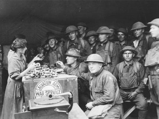 One of The Salvation Army Doughnut Girls hands out homemade doughnuts to World War I troops.