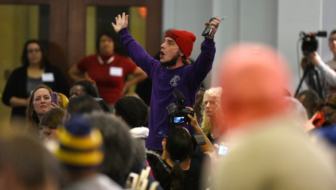 Adam Murphy, of Flint, shouts about his family's health issues during the Flint Water Town Hall meeting.