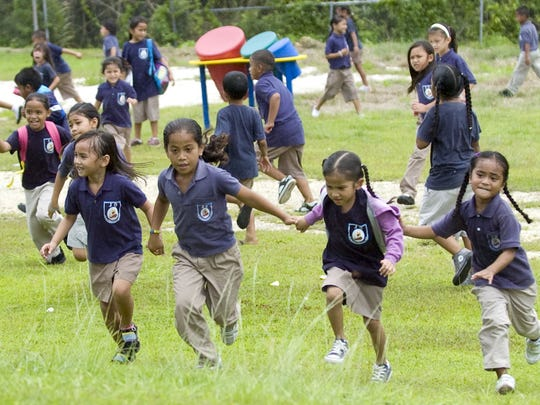 In this file photo, students run back from the playground