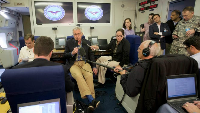 Defense Secretary Chuck Hagel, center,  speaks to members of the media during his flight to Afghanistan on June 1, 2014.