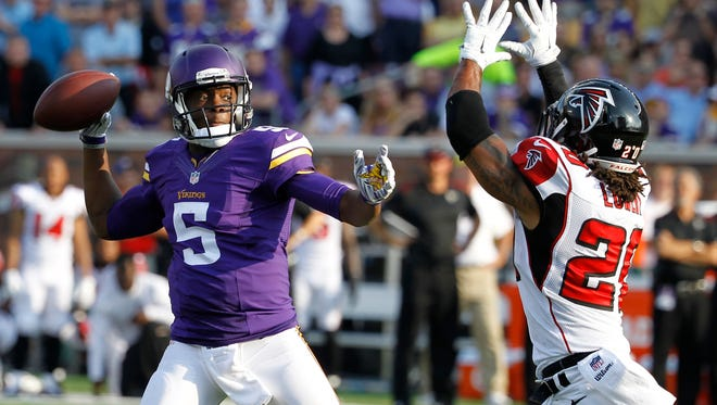 Minnesota Vikings quarterback Teddy Bridgewater (5) looks to pass over Atlanta Falcons free safety Dwight Lowery during the first half of an NFL football game, Sunday, Sept. 28, 2014, in Minneapolis. (AP Photo/Ann Heisenfelt)