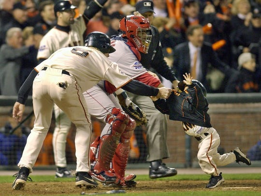 J.T. Snow, left, drags 3-year-old Darren Baker, son of then-Giants manager Dusty Baker, away from home plate.
