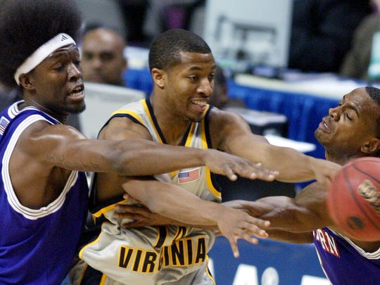 West Virginia's Darris Nichols (center) is defended by Northwestern States forward Clifton Lee (left) and Tyronn Mitchell in the 2006 NCAA Tournament. NSU's historic season ended with a loss to the Mountaineers.