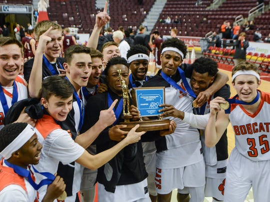 DaJon Simpson, bottom left, celebrates the Bobcats' District 3 Class 5-A championship win over Mechanicsburg in the 2016-17 season.