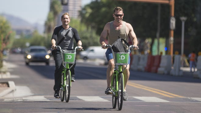 Wes Waggener (left) and Paul Coseo  ride after getting the bikes from the Phoenix bike-sharing program downtown on July 9, 2016 in Phoenix, Ariz.
