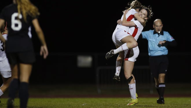 Leon's Maddie Powell is hugged by a teammate after scoring a goal on a penalty kick against Navarre during a 2015 playoff game.