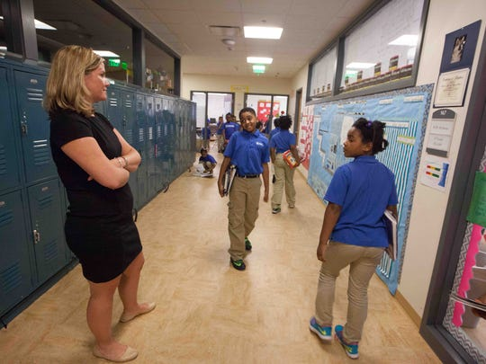 Kuumba Academy's school leader, Sally Maldonado, observes her students in the hallway.