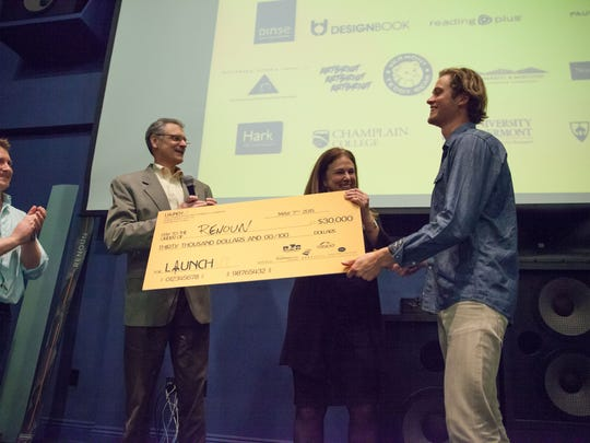 Cyrus Schenck accepts a $30,000 on behalf of Renon at LaunchVT at the Main Street Landing on Thursday in Burlington.