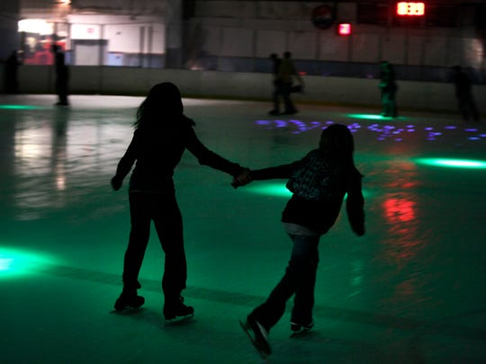 Two young girls skate hand in hand during a Friday night open skate to lights and music at Lakeshore Hockey Arena in 2011.