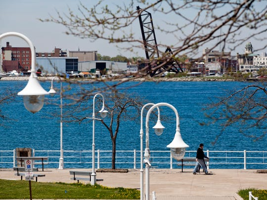 People walk along the river front at Paul Blundy Park Thursday.