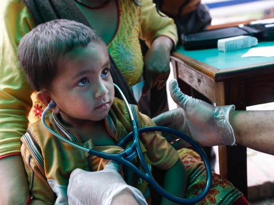 Five-year-old Suran Laishwa listens to his own heartbeat. Medical staff from the Delaware Medical Relief Team saw more than 300 patients during a clinic at Khwopa Higher Secondary School in Bhaktapur, Nepal, on Saturday. This is the team's first trip since responding to the earthquake in Haiti in 2010.