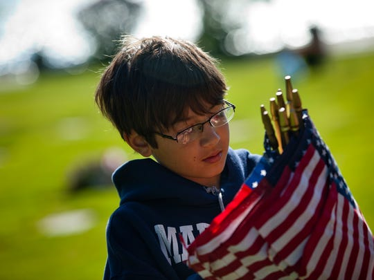 Airrion Hinojosa, 9, of Port Huron, places flags at the graves of veterans along with members of American Legion Post 449 on Saturday at Riverlawn Cemetery in Marysville.