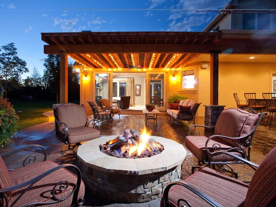 This outdoor bar and natural gas fire pit anchor multiple seating areas on a patio west of Windsor.