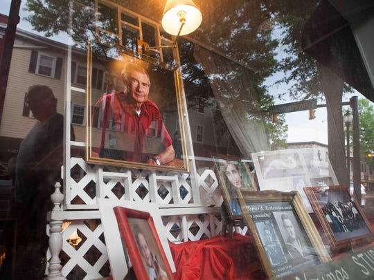 A reflection of a pedestrian who walks by Young's Studio where a picture of Ross Edward Young hangs on dispay. Eric Young, owner of Young's Studio, a 62-year-old photography studio in Dover will close next week.
